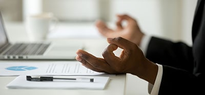 Person sitting at desk, holding hands in a meditation position.