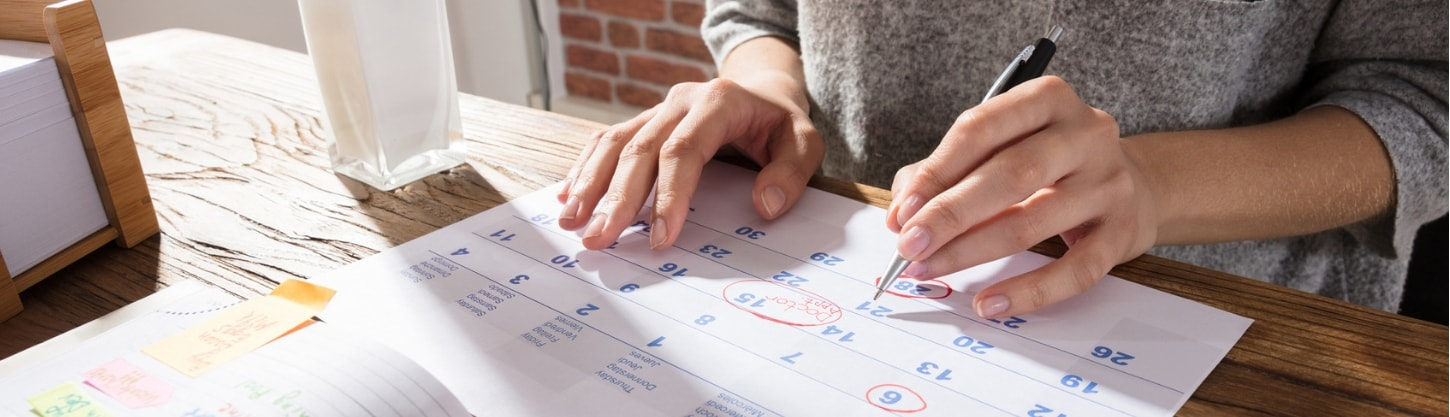 An entrepreneur using a paper planner to manage their tasks and responsibilities.
