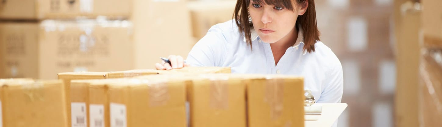 A warehouse manager organizing shipping supplies