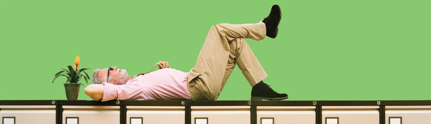 man lying next to a plant on top of a filing cabinet