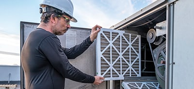 Man wearing a hard hat installing a new air filter.