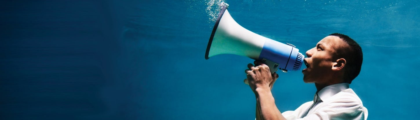 man speaking into megaphone underwater
