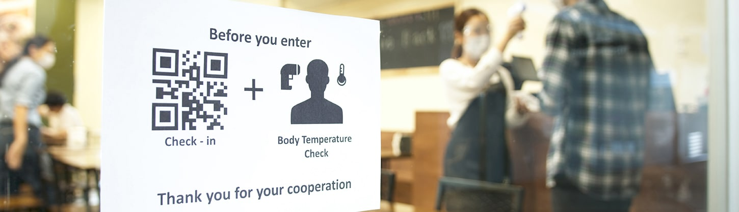 Close-up of a piece of restaurant signage that tells customers they must check in digitally and receive a body temperature check before entering.