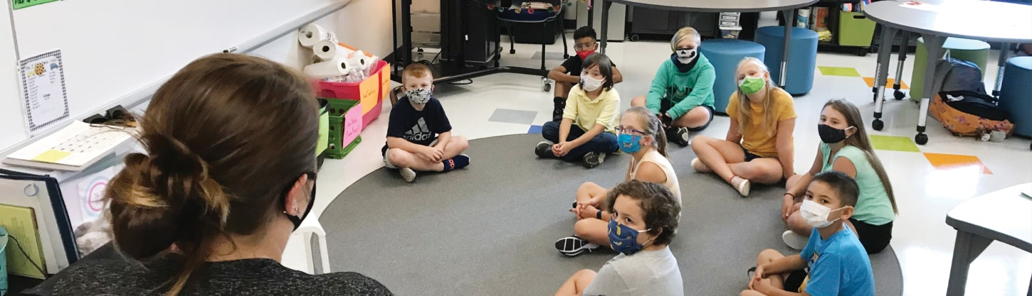 teacher speaking to a classroom of students wearing facial coverings