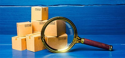 Magnifying glass hovering over a stack of cardboard boxes.