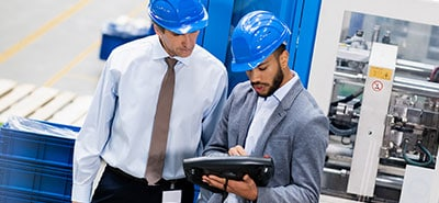 Two men wearing hard hats looking down at a tablet.