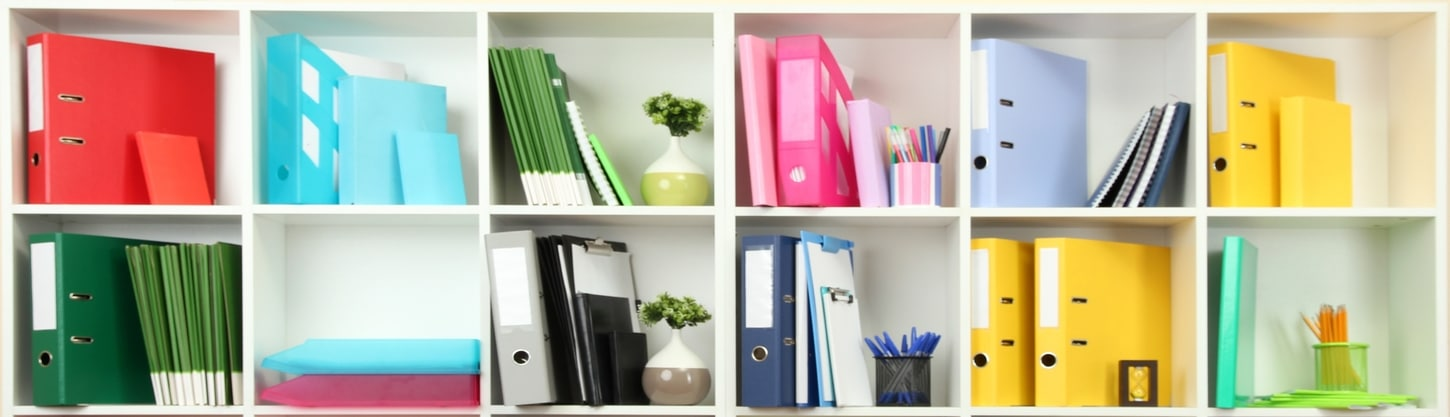 Bookshelves with different color binders, notebooks, pens, etc.
